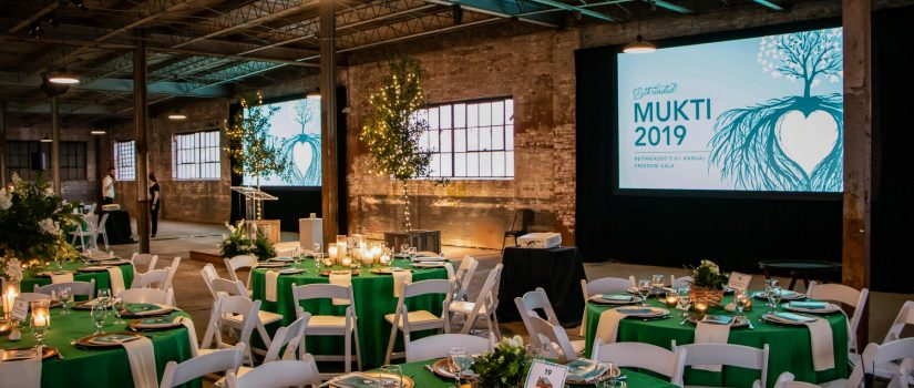 Room setup with chairs and tables for a corporate event with green and gold decorations