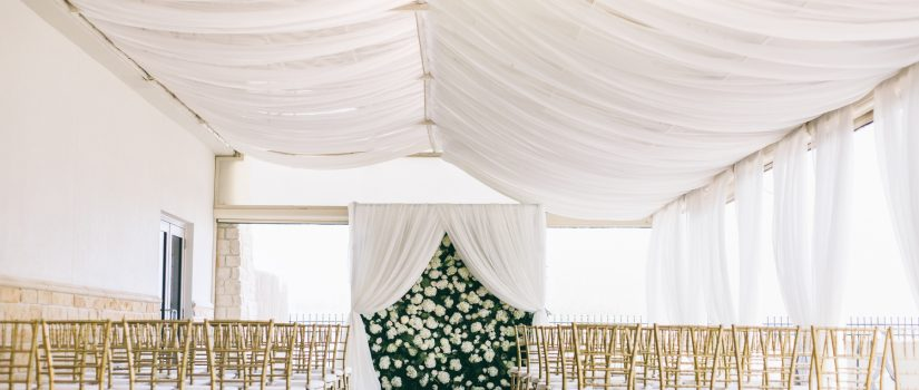 Wedding ceremony setup with wall of white flowers at the end of the isle.