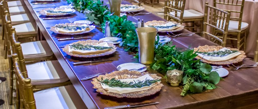 Long wooden tables set up for a community dinner with gold accent decorations.