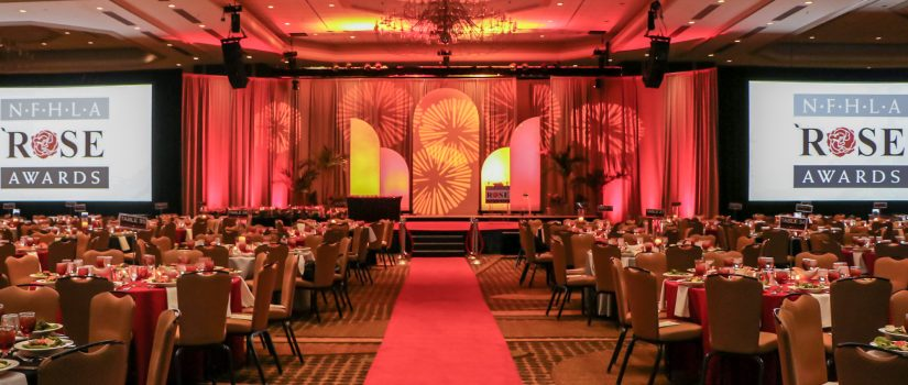 Room set up with chairs and tables for a corporate award gala with red lighting for decoration.