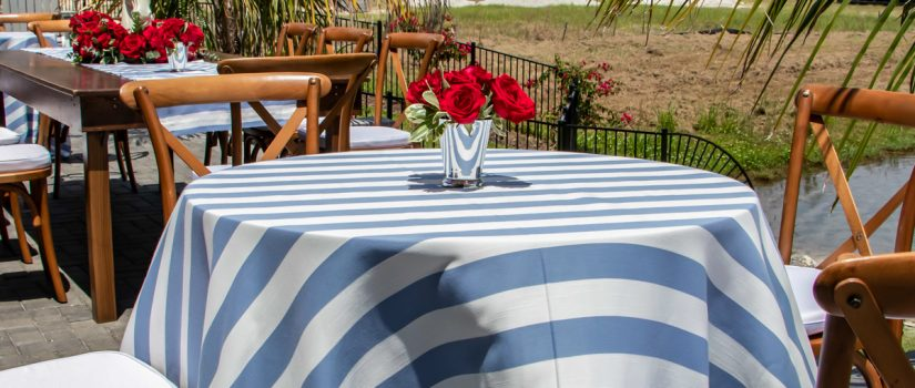 Striped table cloth with red flower center pieces and wooden chairs