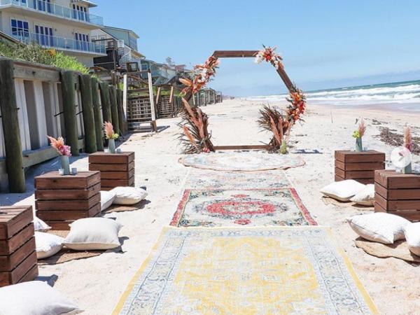 Boho themed wedding isle with hexagon arch on the beach